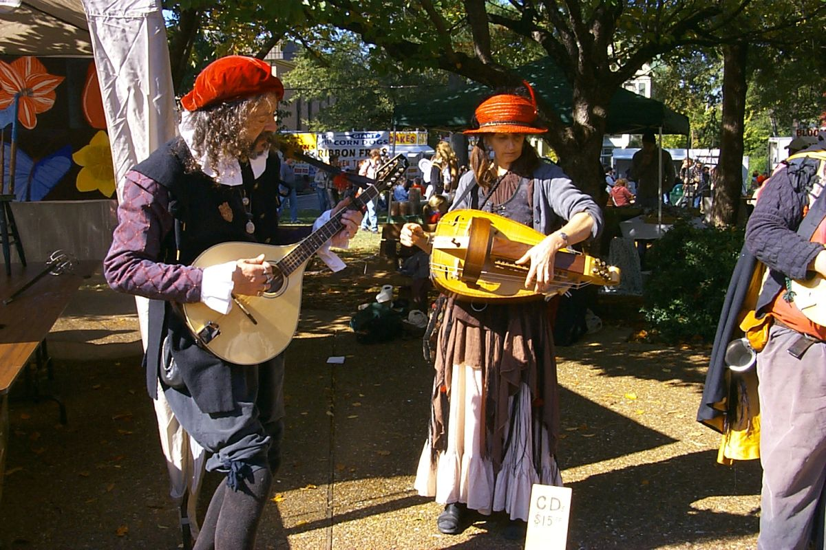 A man and a woman who are playing musical instruments at Arts Alive.
