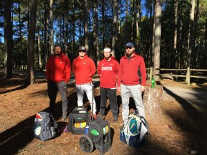 Four men standing beside their disc golf gear before they play a game of disc golf at the newest course at McFarland Park in Florence, Alabama.