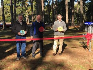 Three men smiling holding discs for the ribbon cutting of the new disc golf course at McFarland Park in Florence, Alabama.